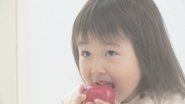 Girl eating tomato