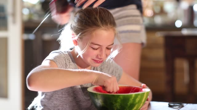 girl eating watermelon at home