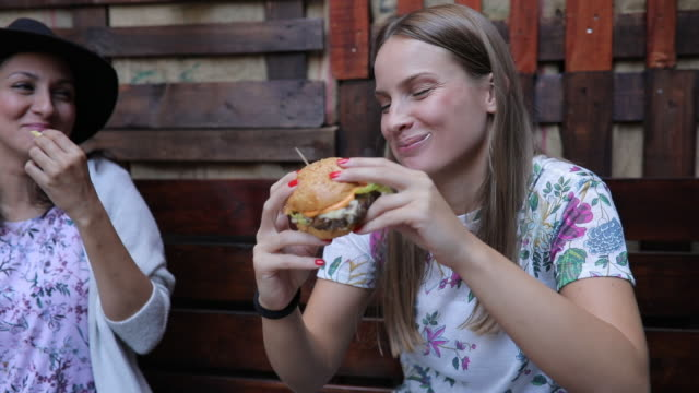 girl eating yummy burger - hamburger stock videos & royalty-free footage