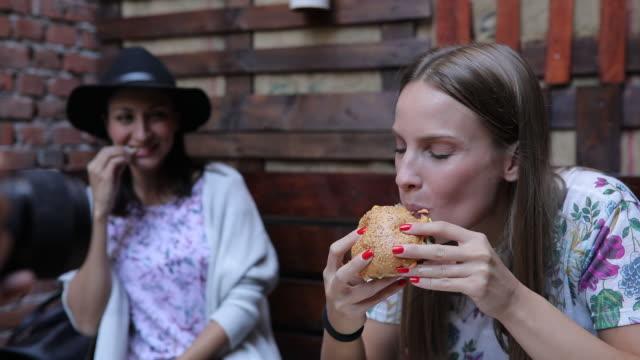 girl eating yummy burger - panino ripieno video stock e b–roll