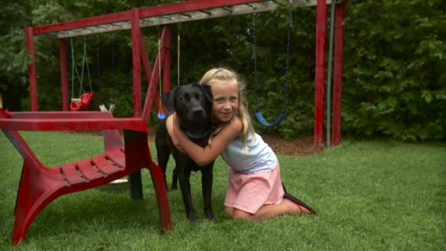 vídeos de stock e filmes b-roll de ws zo girl (8-9) embracing black labrador and stroking in playground / stowe, vermont, usa - 8 9 anos
