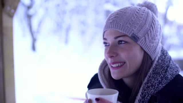 stockvideo's en b-roll-footage met meisje geniet in besneeuwde dag in het bos - warme dranken