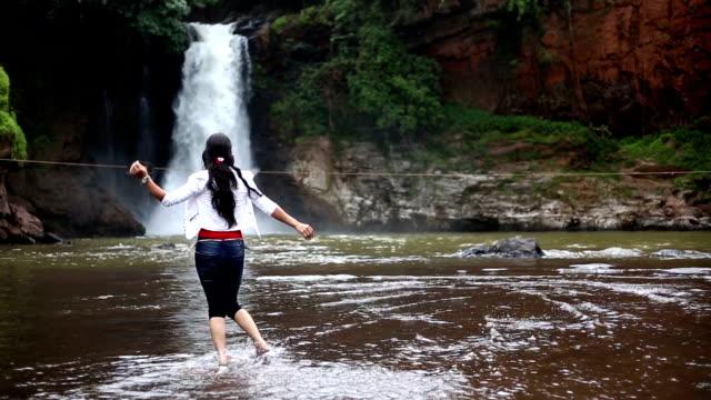 stockvideo's en b-roll-footage met meisje genieten en dansen in de buurt van de waterval - alleen één tienermeisje