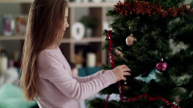 girl enjoying decorating christmas tree - decorating the christmas tree stock videos & royalty-free footage