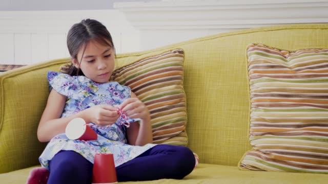 flicka njuter spelar plåtburk telefon n i vardagsrummet hemma, 9 år - sn�� bildbanksvideor och videomaterial från bakom kulisserna