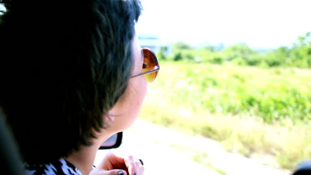 Mädchen genießen Sommerbrise aus dem Autofenster
