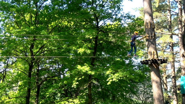 Girl enjoying ziplines walks on a cable, arrives at a tree and changes the safety lines