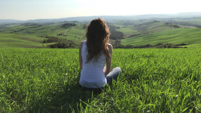 a girl enjoys the view in a wheat field in val d'orcia. asciano, siena - 麦わら帽子点の映像素材/bロール
