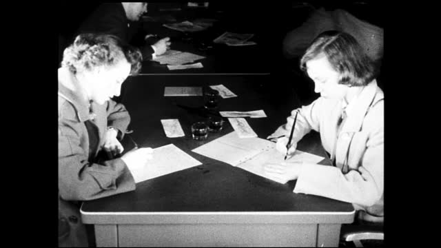 girl enters building, walks upstairs, and approaches reception; girl fills out application form and gives it back to the receptionist - 1940 1949 video stock e b–roll