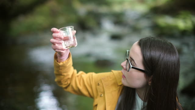 stockvideo's en b-roll-footage met girl explorer collecting a sample of river water and stones for stem research - nieuwsgierigheid