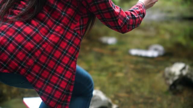girl explorer collecting water sample in a beaker for stem research - プレイドシャツ点の映像素材/bロール