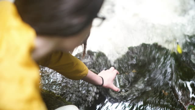 vídeos de stock, filmes e b-roll de girl explorer collecting water sample in a beaker for stem research - amostra científica