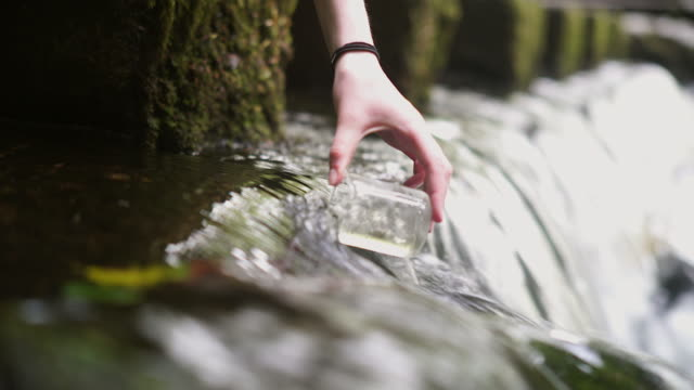 Girl Explorer Collecting Water Sample in a Beaker for STEM research
