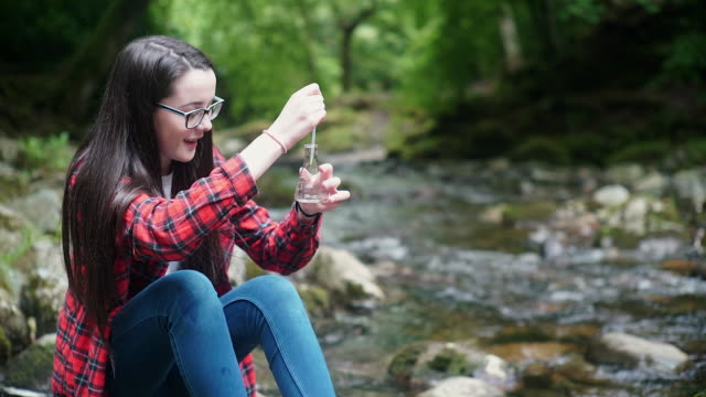 girl explorer collecting water sample in a flask for stem research - environmentalist stock videos & royalty-free footage