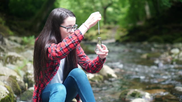 girl explorer collecting water sample in a flask for stem research - one teenage girl only stock videos & royalty-free footage