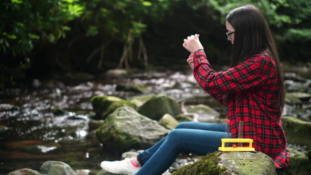 girl explorer collecting water sample in a test tube for stem research - プレイドシャツ点の映像素材/bロール