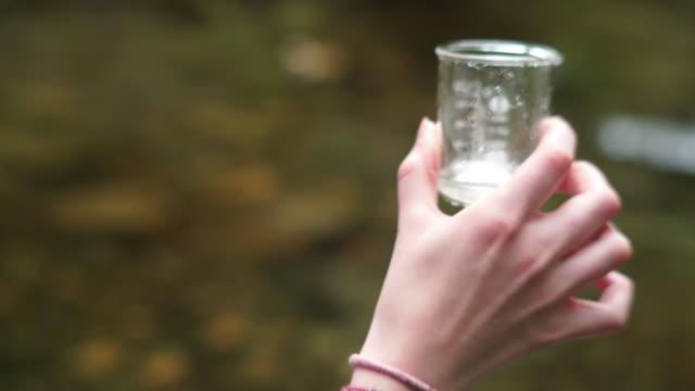 vídeos de stock, filmes e b-roll de girl explorer inspecting a water sample in a beaker for stem research - amostra científica