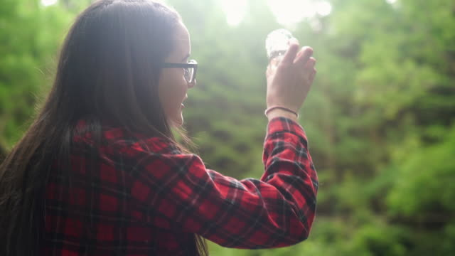 girl explorer inspecting a water sample in a beaker for stem research - one teenage girl only stock videos & royalty-free footage