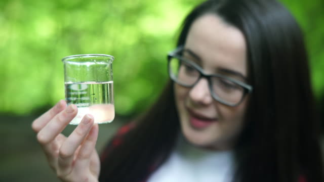 girl explorer inspecting a water sample in a beaker for stem research - scientific sample stock videos & royalty-free footage