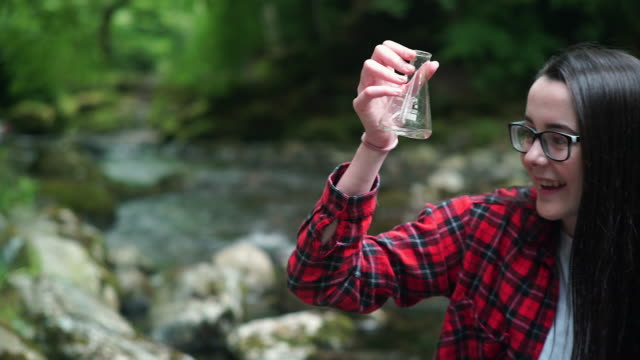 Girl Explorer Inspecting a Water Sample in a Flask for STEM research