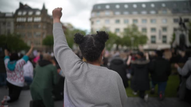 girl extends her arm and clenches her fist in a gesture of solidarity while protesters attend a second day of black lives matter demonstrations in... - arms raised stock videos & royalty-free footage