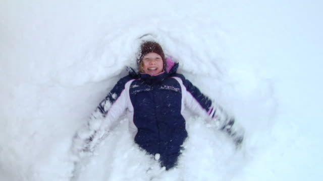 oh ms slo mo girl falling backward into snow and making snow angel/ hortonville, wisconsin - winter video stock e b–roll