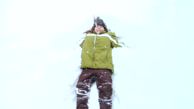 OH MS SLO MO Girl falling backward into snow and making snow angel/ Hortonville, Wisconsin