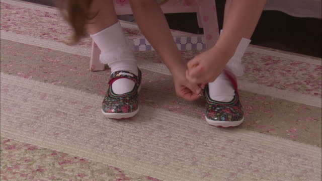 stockvideo's en b-roll-footage met cu td tu girl fastening strap on her shoes and smiling / westfield, new jersey, usa - klem
