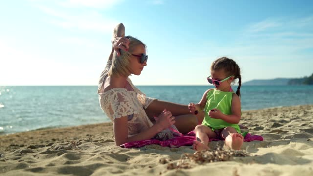 girl feeding her mother on the beach - sunglasses stock videos & royalty-free footage