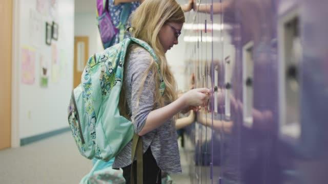 girl fidgeting with the lock on her locker - locker stock videos and b-roll footage