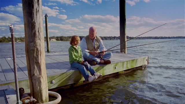 Girl fishing with grandfather on dock