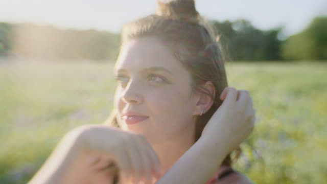 ms slo mo. girl flips her hair and looks at camera in field of flowers. - chignon video stock e b–roll