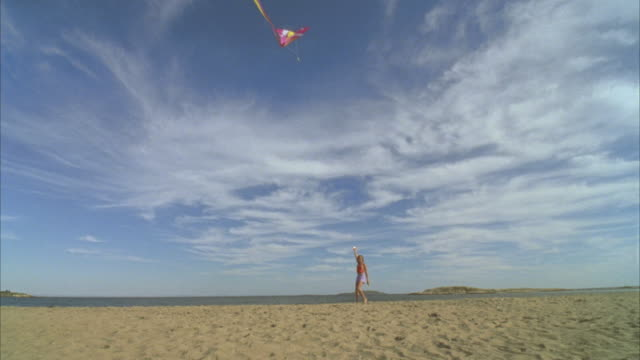 la ws girl flying kite and running with boy across beach / phippsburg, maine, usa  - kite toy stock videos and b-roll footage