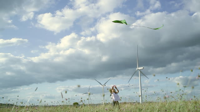 ms girl flying kite in wind farm / toulouse, midi-pyrenees, france - kid with kite stock videos & royalty-free footage