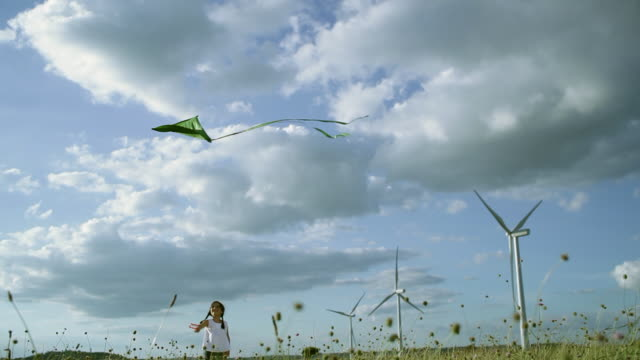 MS Girl flying kite in wind farm / Toulouse, Midi-Pyrenees, France