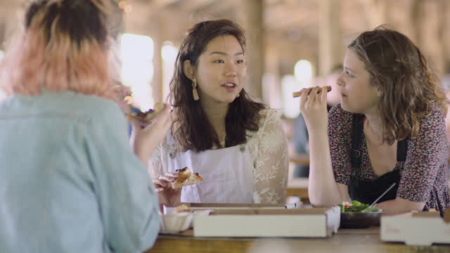ws. girl friends chat and eat pizza together in restaurant picnic shelter. - meal stock videos and b-roll footage