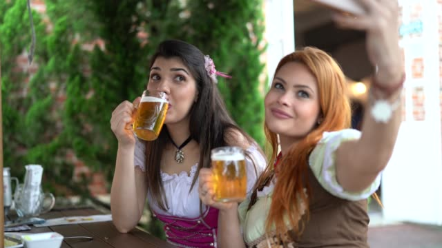 girl friends taking a selfie drinking a beer at pub - brasile video stock e b–roll