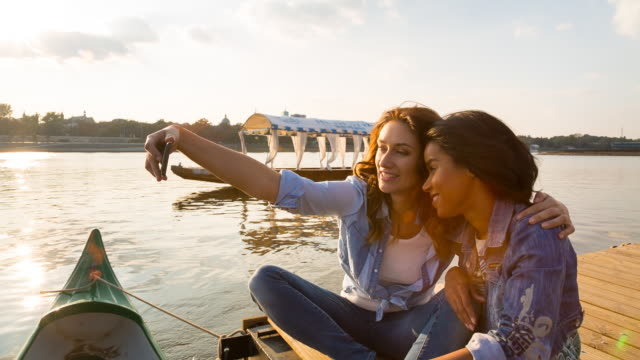 vídeos de stock, filmes e b-roll de ms girl friends taking selfie photo on wooden dock by river - jaqueta jeans