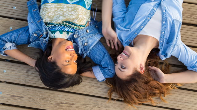 vídeos de stock, filmes e b-roll de ms ha girl friends talking and laughing on wooden dock, top view - jaqueta jeans