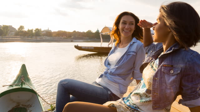 MS girl friends talking and laughing on wooden dock