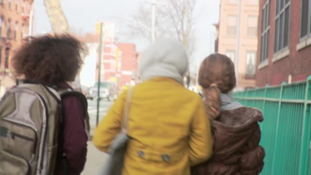 Girl friends walking along street