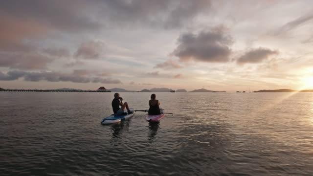 vídeos de stock, filmes e b-roll de amigas de meninas assistindo belo pôr do sol de paddleboard no mar férias tropicais - copy space