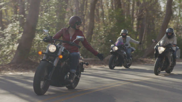 slo mo. girl gang on motorcycles use hand signals to communicate on wooded highway drive. - motorradfahrer stock-videos und b-roll-filmmaterial