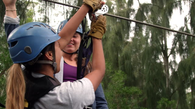 a girl gets hooked up onto a zipline - kahuku stock videos & royalty-free footage