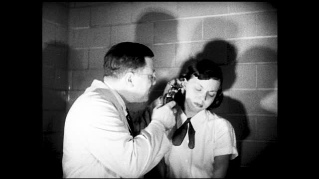 "vidéos et rushes de girl gets weighed on scale and measured for height by nurse; girl getting blood pressure checked by nurse, sign on door ""medical examination""; knee... - 1940 1949"