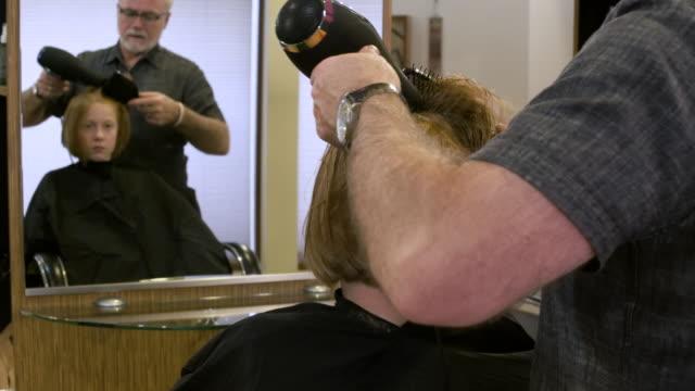 vídeos y material grabado en eventos de stock de girl getting her hair dried by a hairdresser - cepillo para el cabello