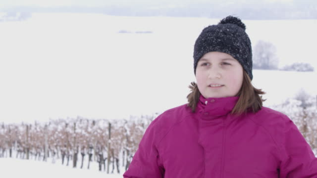 4K Girl getting hit with snowball in snowy vineyard, slow motion