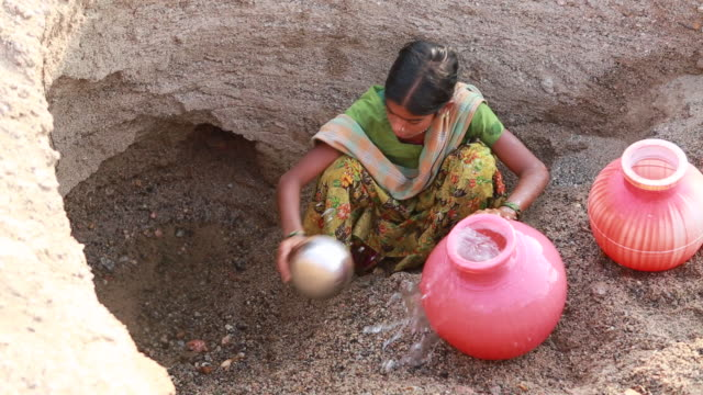 Girl getting water out of an almost empty waterhole near Pannur, India