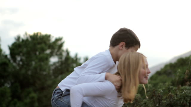 girl giving boy a piggyback ride in nature. - piggyback stock videos & royalty-free footage