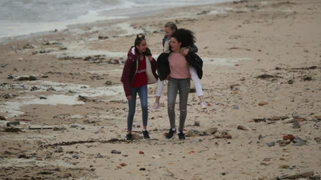 girl giving friend piggyback on windy beach - beach stock videos & royalty-free footage